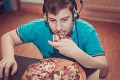Adolescente que come la pizza que se sienta en un ordenador portátil Fotos de archivo