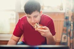 Adolescente que come la pizza que se sienta en un ordenador portátil Fotos de archivo libres de regalías