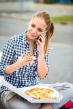 Adolescente que come la pizza y que llama el teléfono Fotografía de archivo libre de regalías