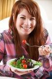 Adolescente que come la placa de la ensalada sana Fotografía de archivo