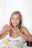 Adolescente que come la rebanada de pan Foto de archivo