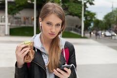 Adolescente que come la torta que mira en teléfono Imagen de archivo libre de regalías