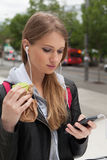 Adolescente que come la torta que mira en teléfono Fotografía de archivo
