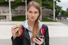 Adolescente que come la torta que mira en teléfono Foto de archivo