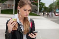 Adolescente que come la torta que mira en teléfono Fotografía de archivo libre de regalías