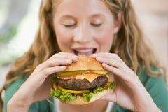 Adolescente que come las hamburguesas Fotos de archivo