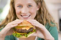 Adolescente que come las hamburguesas Foto de archivo libre de regalías