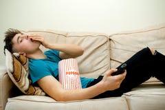 Adolescente que come las palomitas Foto de archivo
