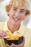 Adolescente que come las patatas fritas Fotos de archivo
