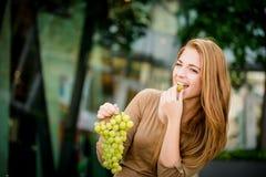 Adolescente que come las uvas Imagenes de archivo