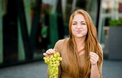 Adolescente que come las uvas Fotos de archivo