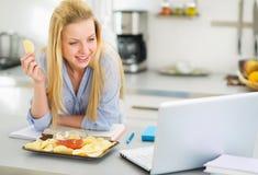 Adolescente que come microprocesadores y que mira en ordenador portátil Fotos de archivo