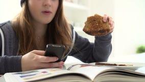 Adolescente que come o café da manhã enquanto enviando a mensagem de texto filme