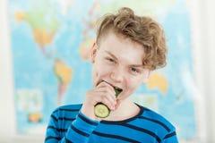 Adolescente que come o pepino inteiro na frente do mapa fotografia de stock royalty free