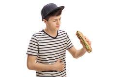 Adolescente que come un bocadillo y que experimenta dolor de estómago Foto de archivo