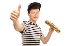 Adolescente que come un bocadillo y que hace un pulgar encima de la muestra Imagenes de archivo