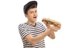 Adolescente que come un bocadillo y que mira la cámara Imagen de archivo