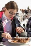 Adolescente que come una crepe deliciosa con el plátano y el chocolate en montañas Un restaurante colocado en una cuesta del esqu fotos de archivo libres de regalías