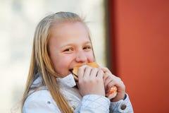 Adolescente que come una hamburguesa Imágenes de archivo libres de regalías