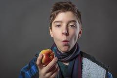 Adolescente que come una manzana Imagenes de archivo
