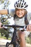 Adolescente que completa un ciclo a través de campo Imagen de archivo libre de regalías