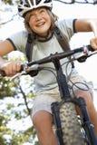 Adolescente que completa un ciclo a través de campo Fotografía de archivo