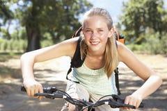 Adolescente que completa un ciclo a través de campo Foto de archivo