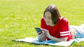 Adolescente que comprueba el tel?fono en la hierba almacen de metraje de vídeo