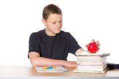 Adolescente que comtempla una manzana roja madura Fotografía de archivo