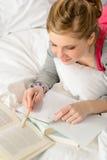 Adolescente que concentra en estudiar en cama Foto de archivo