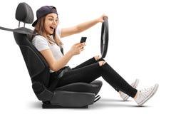 Adolescente que conduce y que mira su teléfono Fotos de archivo libres de regalías