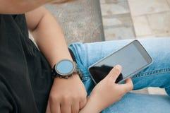 Adolescente que conecta su smartwatch con su smartphone Imagen de archivo