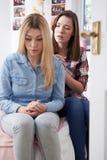 Adolescente que conforta al amigo infeliz en dormitorio Fotografía de archivo