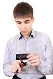 Adolescente que corta una tarjeta de crédito Foto de archivo