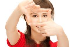Adolescente que crea un marco con los fingeres Imágenes de archivo libres de regalías