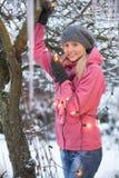 Adolescente que cuelga luces de hadas en árbol Fotos de archivo libres de regalías
