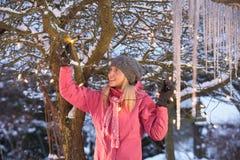 Adolescente que cuelga luces de hadas en árbol con Ici Imagen de archivo libre de regalías