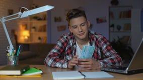 Adolescente que cuenta los billetes de banco euro que piensan en la nueva compra, soñando metrajes