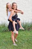 Adolescente que da a hermana un paseo del transporte por ferrocarril Imagen de archivo libre de regalías