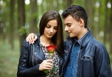 Adolescente que da una flor a su novia Imagenes de archivo