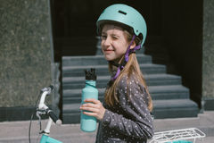Adolescente que descansa en una calle con un agua potable de la bicicleta Imagenes de archivo