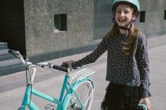 Adolescente que descansa en una calle con una bicicleta Imagen de archivo libre de regalías