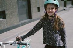 Adolescente que descansa en una calle con una bicicleta Fotos de archivo