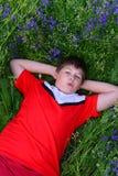 Adolescente que descansa sobre césped con las flores azules Fotografía de archivo