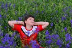 Adolescente que descansa sobre césped con las flores azules Imagen de archivo libre de regalías