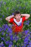 Adolescente que descansa sobre césped con las flores azules Imagen de archivo