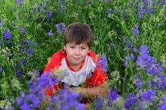 Adolescente que descansa sobre césped con las flores azules Foto de archivo libre de regalías