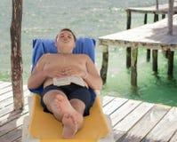 Adolescente que descansa sobre el embarcadero Foto de archivo