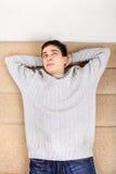 Adolescente que descansa sobre el sofá Imagenes de archivo
