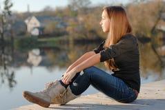 Adolescente que descansa sobre la orilla del río Fotos de archivo libres de regalías